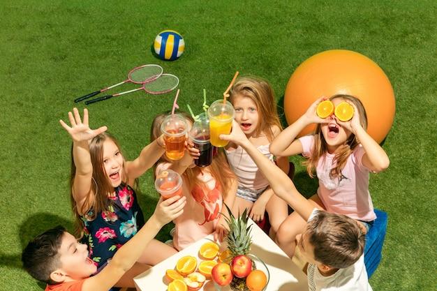 De groep tienerjongens en meisjes die op groen gras bij park zitten Gratis Foto