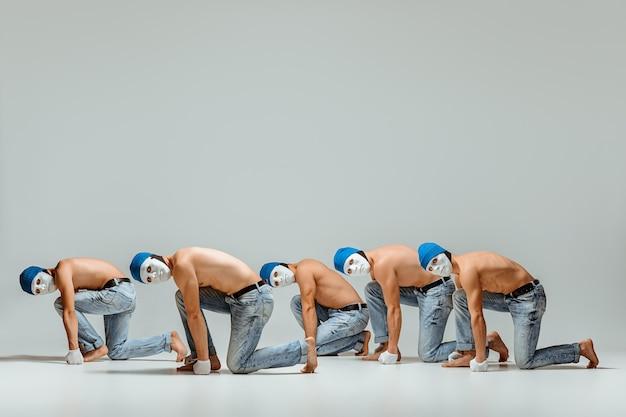 De groep van blanke mannen in witte maskers en hoeden, jeans