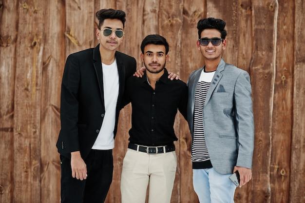 De groep van drie toevallige jonge indiërs bemant gesteld tegen houten achtergrond.