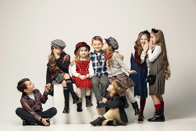 De groep van mooie tiener meisjes en jongens op een pastel. stijlvolle jonge tiener meisjes poseren. klassieke herfststijl. tiener en kinderen mode-concept. kinderen fasion concept