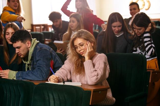 De groep van vrolijke gelukkig studenten zitten in een collegezaal voor de les