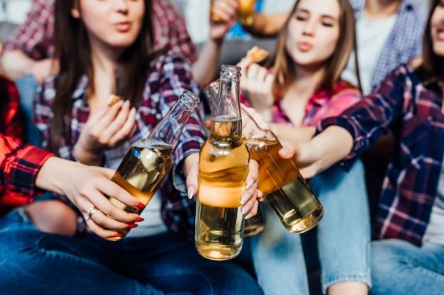 De groep vrienden die met bier binnen interiour toejuichen, sluit omhoog.