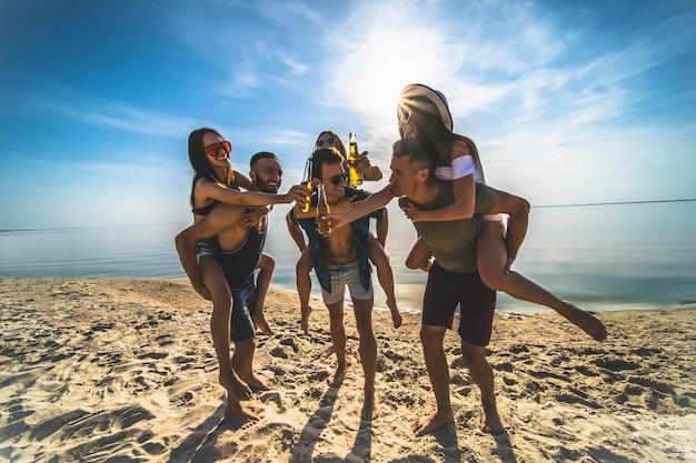 De groep vrienden die plezier hebben op het strand