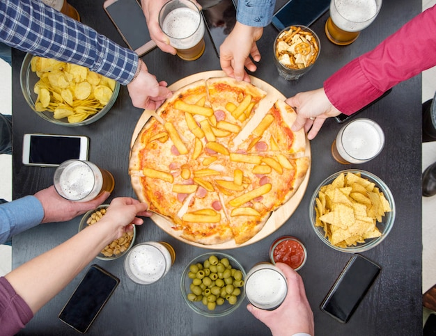 De groep vrienden drinkt bier, eet pizza, spreekt en glimlacht terwijl thuis het rusten