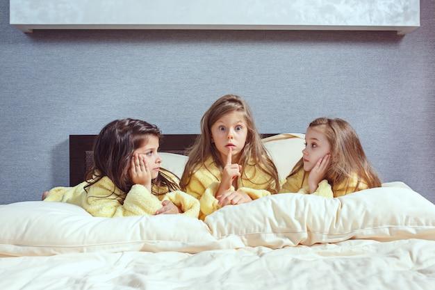 De groep vriendinnen die googtijd op bed nemen