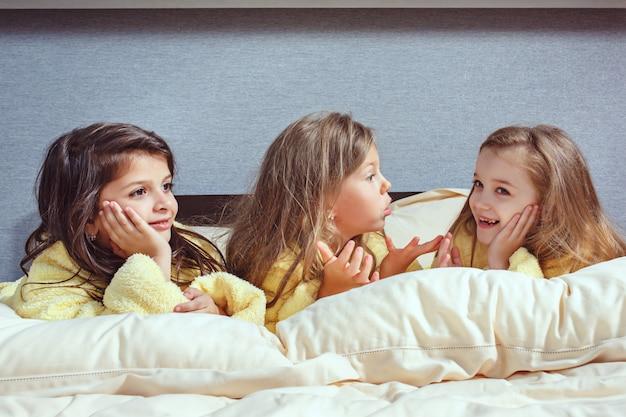 De groep vriendinnen die lekker op bed liggen