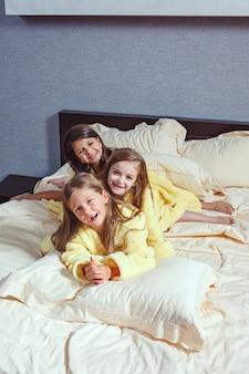 De groep vriendinnen die lekker op bed liggen.