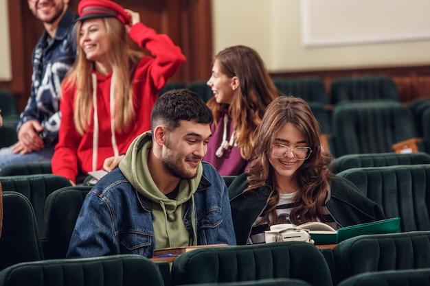 De groep vrolijke gelukkige studenten die vóór les in een collegezaal zitten