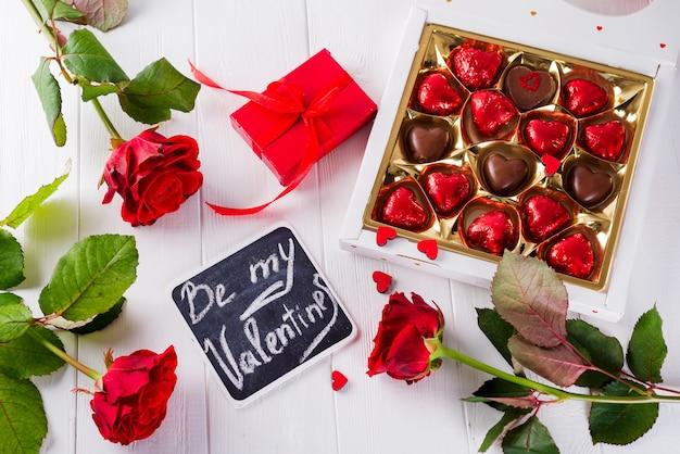 De groetkaart van de valentijnskaartendag met rode rozen en hart gevormde chocolade