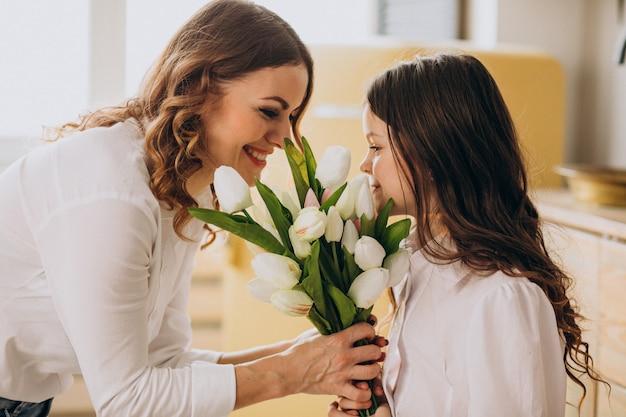 De groetmoeder van het meisje met bloemen op moedersdag