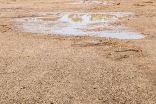 De grond van de close-upoppervlaktegrond na regen met de geweven achtergrond van bandtekens