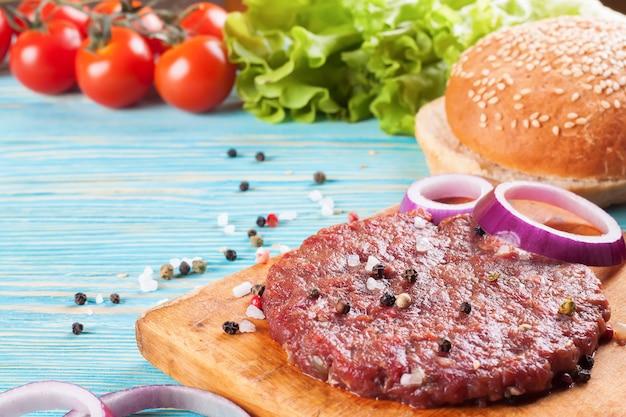 De grondstoffen voor de zelfgemaakte hamburger op blauwe houten tafel.