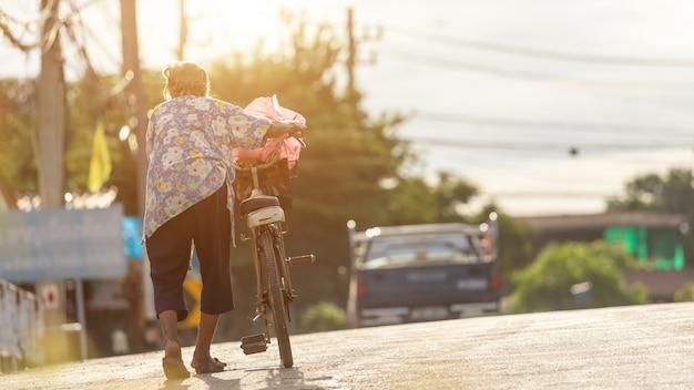 De grootmoeder die met oude fiets op de straat loopt