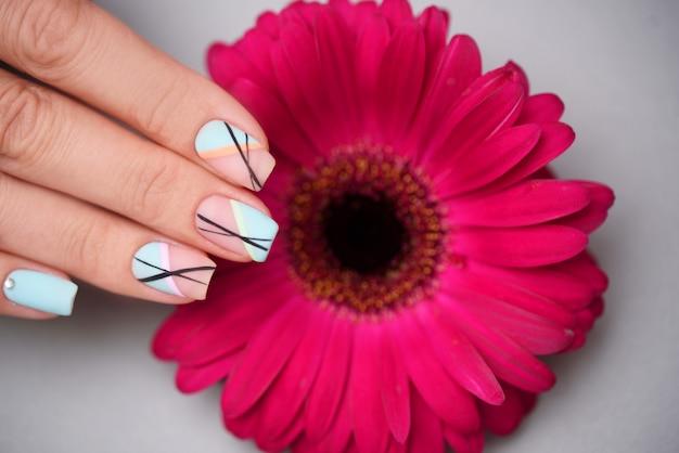 De grote manicure met bloem in schoonheidssalon, sluit omhoog