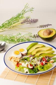 De grote salade bestaat uit gesneden avocado, gekookt ei, sla, sla, tomaat en koekjes, gegarneerd met slaroom, avocado doormidden gesneden op de rug, een maaltijd met veel groenten.