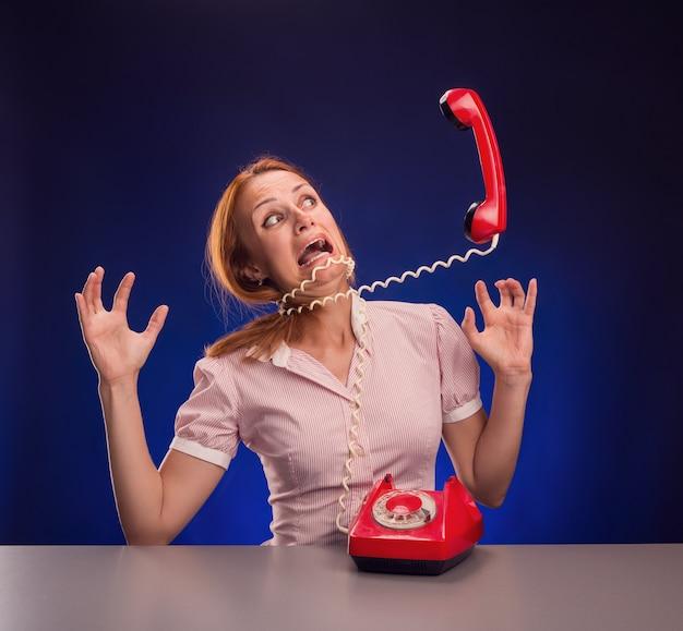 De grote telefoon schreeuwt tegen de vrouw