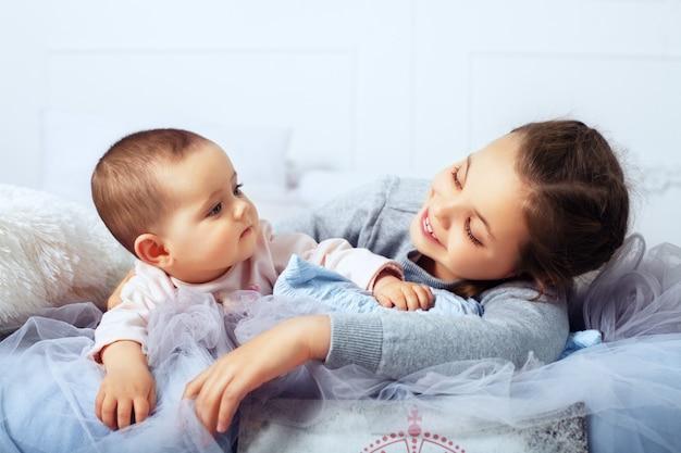 De grote zus ligt met de baby in bed. het concept van familie en levensstijl.