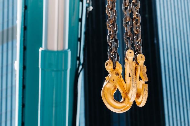 De haken van de mobiele kraan bij het glas van hoge gebouwen. veel haken die aan kettingen hangen die aan een kraan hangen.