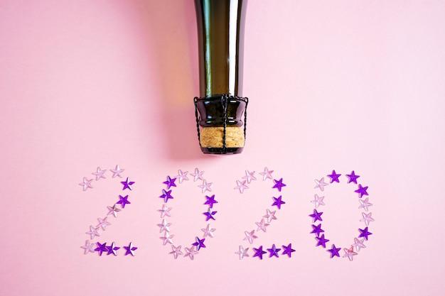 De hals van een fles champagne en een glas op een pastelroze oppervlak. in de omgeving zijn roze en paarse steentjes in de vorm van sterren en maak het nummer 2020.