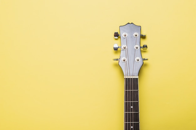 De hals van een klassieke zes-snarige gitaar op een geel oppervlak