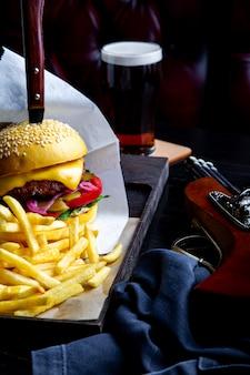 De hamburger en de frieten van het ambachtrundvlees op lijst in restaurant met glas bier op dark. modern fastfood lunchframe