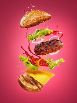 De hamburger met vliegende ingrediënten op roze achtergrond. reclame concept