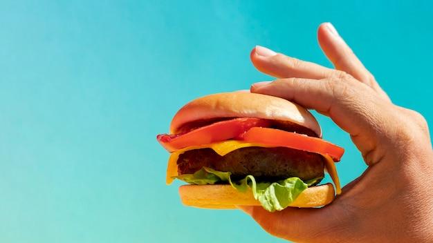 De hamburger van de de persoonsholding van de close-up met exemplaar-ruimte