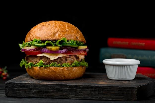 De hamburger van de rundvleescotlet met saus op een houten raad