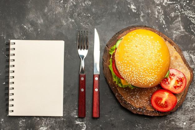 De hamburger van het bovenaanzichtvlees met groenten en kaas op de donkere sandwich van het bureaubroodje