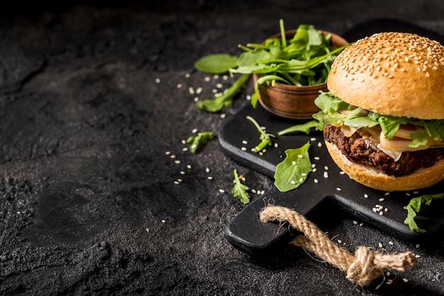 De hamburger van het hoge hoekbacon met salade en exemplaar-ruimte
