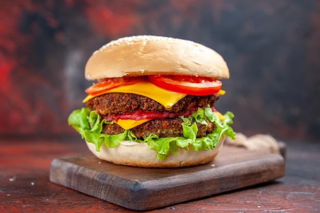De hamburger van het vooraanzichtvlees met kaassalade en tomaten op donkere vloer