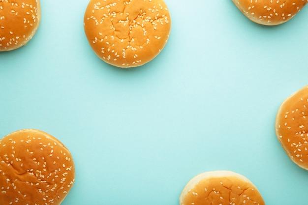 De hamburgerbroodjes op een blauwe achtergrond. bovenaanzicht.