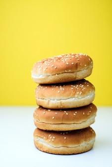 De hamburgerbroodjes op witte en gele achtergrond