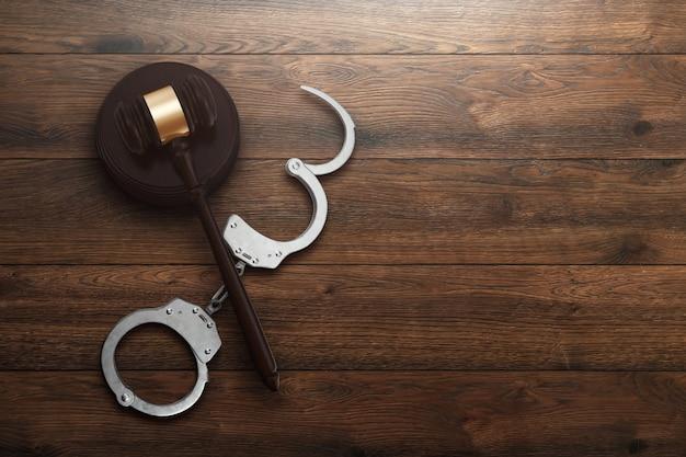 De hamer en handcuffs van de rechter op houten achtergrond