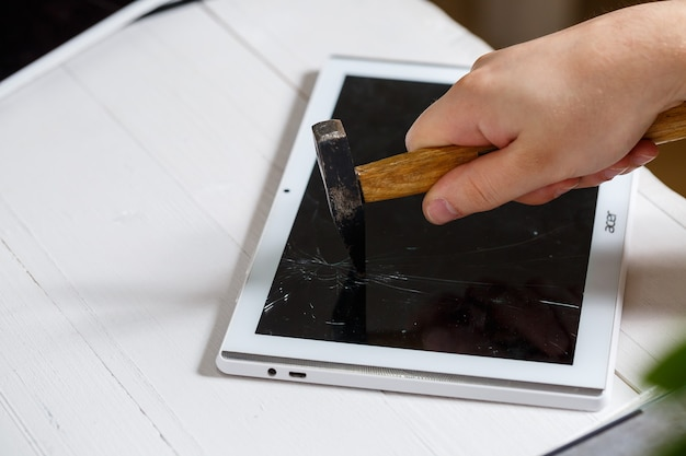 De hamer raakt de kapotte touchscreen-tablet, wat suggereert dat deze op het punt staat deze te vervangen. reparatie van gebroken glazen tablet