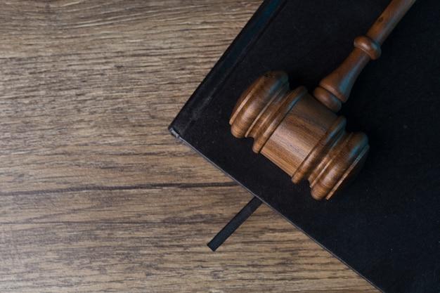 De hamer van de rechter ligt op een zwart notitieboekje aan het bureau