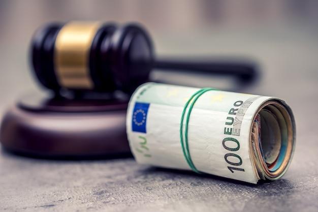 De hamerhamer van de rechter. justitie en euro geld. euro valuta. hofhamer en gerolde euro bankbiljetten. vertegenwoordiging van corruptie en omkoping in de rechterlijke macht.