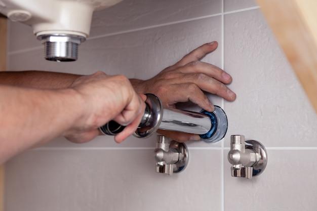 De hand bevestigende gootsteen van de close-up mannelijke loodgieter in badkamers met tegelmuur. professionele reparatie van sanitair, installatie van waterleidingen. moersleutel in hand man gemonteerd rioolafvoer