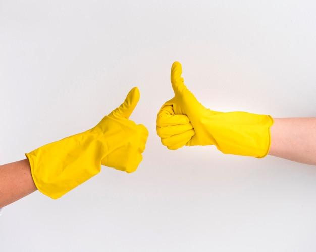 De hand die beschermende handschoenen draagt beduimelt omhoog