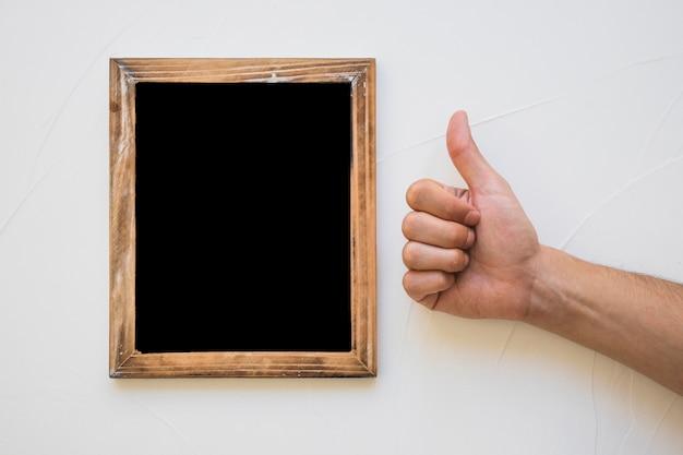 De hand die duim toont ondertekent dichtbij het bord