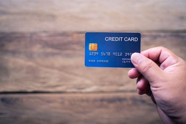 De hand die een creditcard houdt doet online aankopen en voert financiële transacties uit.