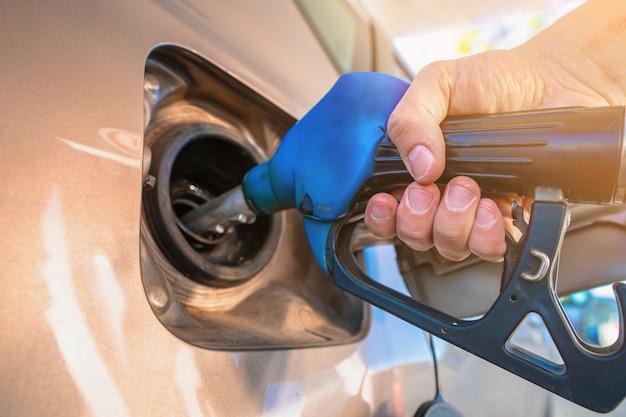 De hand die het pistool tankstation vasthoudt om de auto bij te tanken