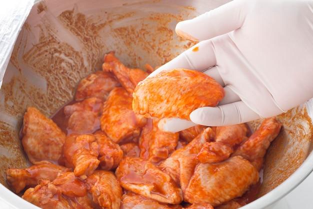 De hand die ruwe kippenvleugels in kruid houden treft voor het koken voorbereidingen