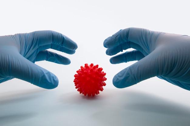 De hand die van de arts het rode concept van de virusbal houdt