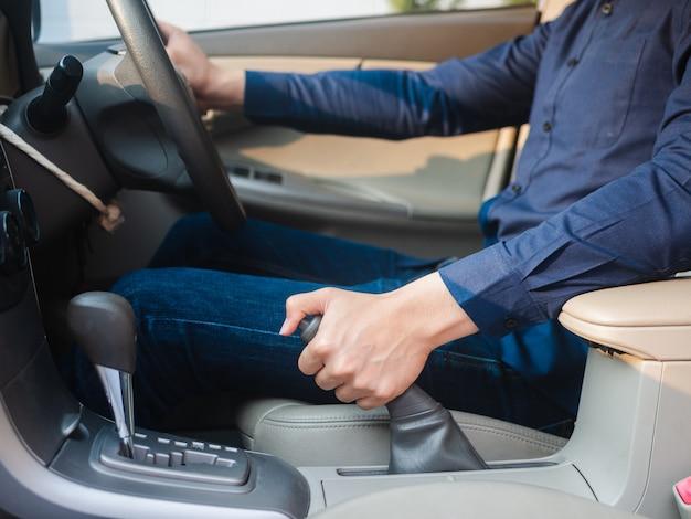 De hand die van de bestuurder de handrem in een auto trekt