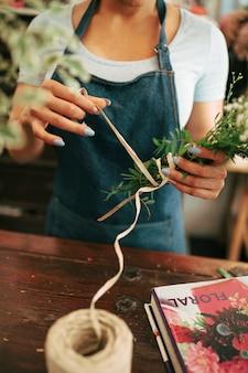 De hand die van de bloemist bos van bloemen maakt