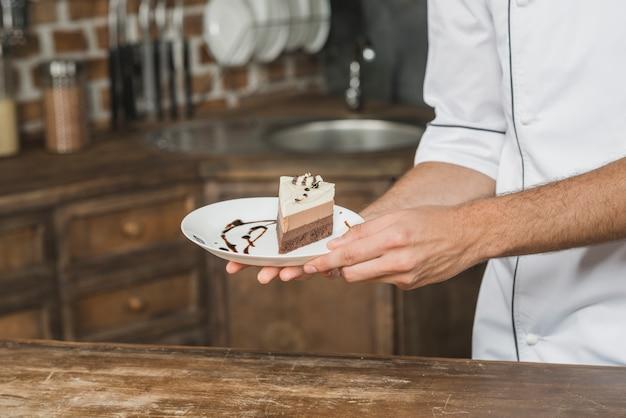De hand die van de chef-kok dessertbord voorstelt