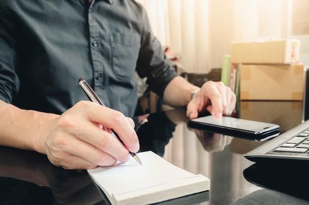 De hand die van de close-upmens op notitieboekje met pen schrijven terwijl het werken bij bureau.