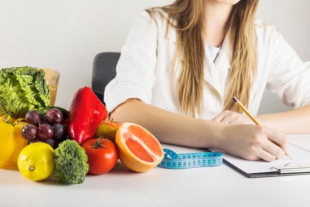 De hand die van de diëtist op klembord met gezond voedsel op bureau schrijft