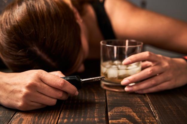 De hand die van de dronken vrouw een glas alcohol en een autosleutel houdt. concept van alcoholisme en verkeersongevallen veroorzaakt door alcohol.
